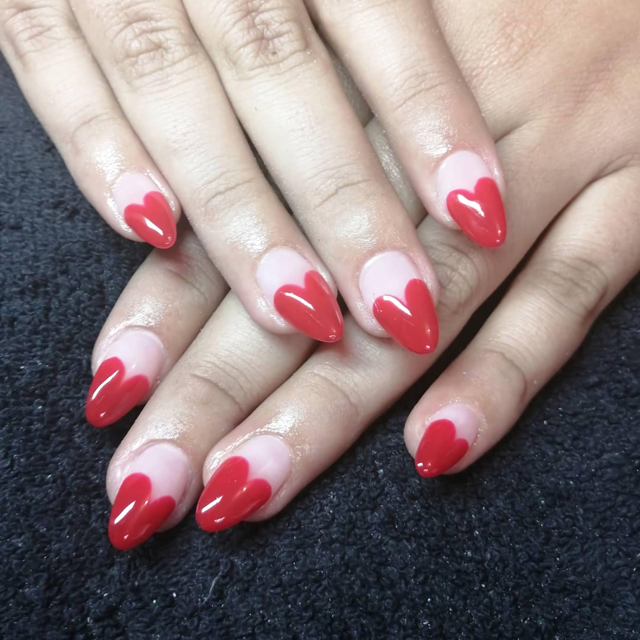 белые ногти с красными сердечками в стиле французского маникюра